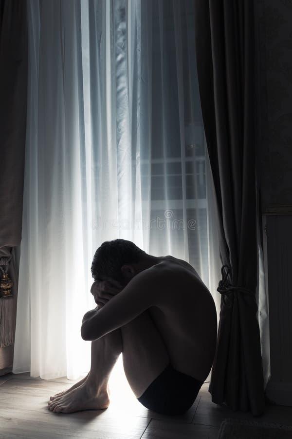 Młody smutny mężczyzna obsiadanie w ciemnym pokoju blisko okno zdjęcia royalty free