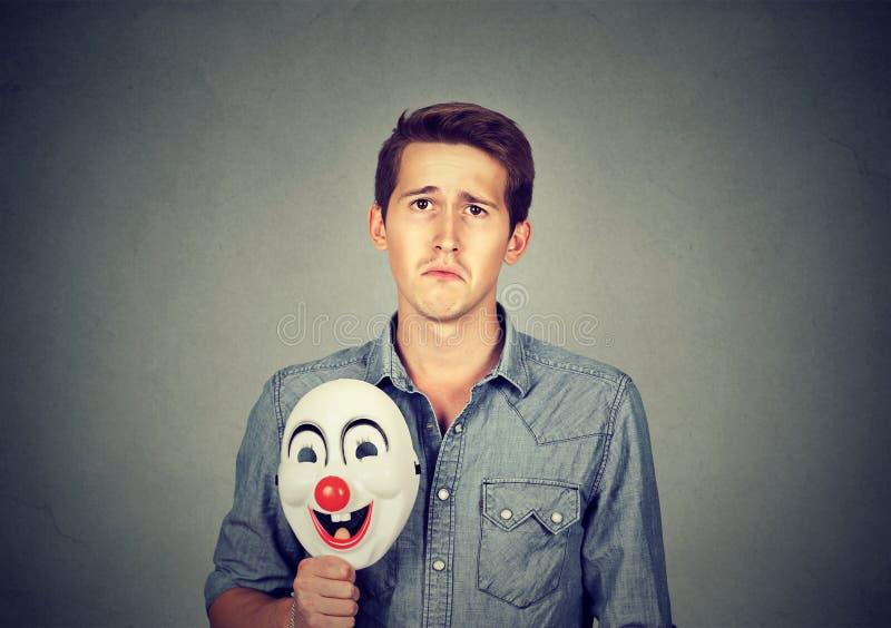 Młody smutny mężczyzna z szczęśliwą błazen maską obraz royalty free