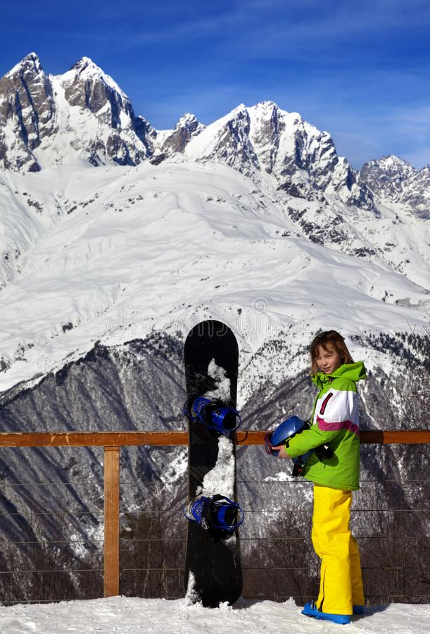 Młody snowboarder z hełmem w rękach i snowboard na viewpoin zdjęcie stock