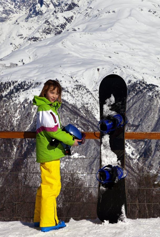 Młody snowboarder z hełmem w rękach i snowboard na viewpoin zdjęcia royalty free