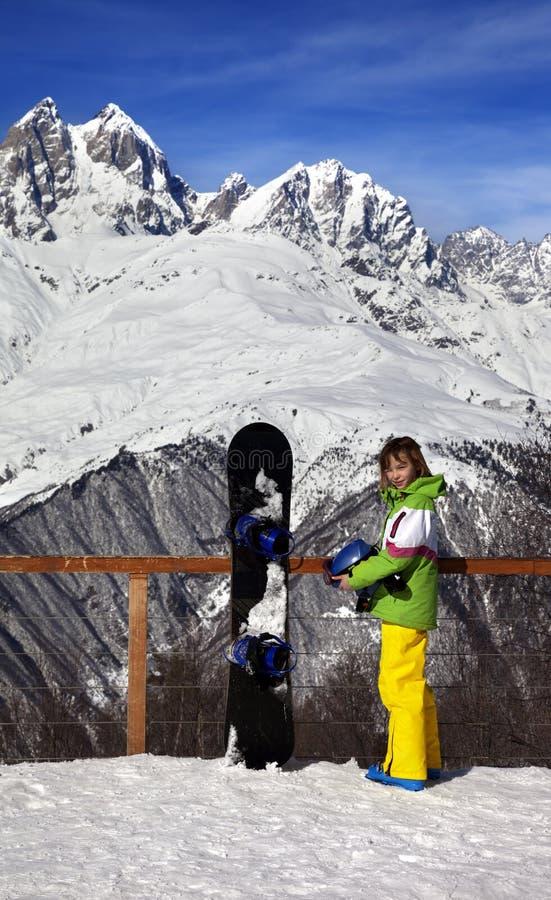 Młody snowboarder z hełmem w rękach i snowboard na viewpoin obrazy stock