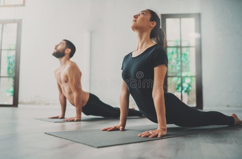 Młody sportive mężczyzna i kobieta ćwiczymy joga ćwiczenia w studiu Para młodzi sporty ludzie ćwiczy joga obrazy stock