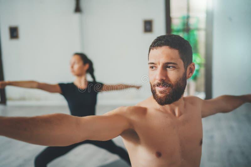 Młody sportive mężczyzna i kobieta ćwiczymy joga ćwiczenia w studiu Para młodzi sporty ludzie ćwiczy joga obrazy royalty free