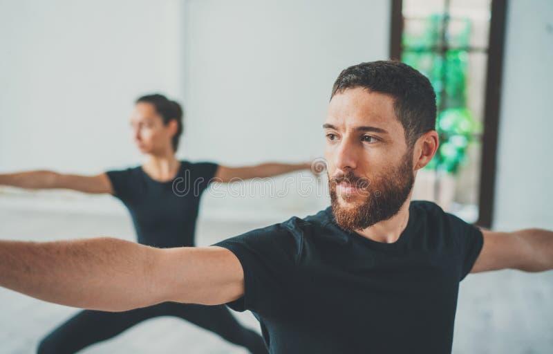 Młody sportive mężczyzna i kobieta ćwiczymy joga ćwiczenia w studiu Para młodzi sporty ludzie ćwiczy joga zdjęcia royalty free