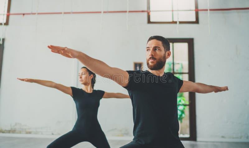 Młody sportive mężczyzna i kobieta ćwiczymy joga ćwiczenia w studiu Para młodzi sporty ludzie ćwiczy joga obraz royalty free