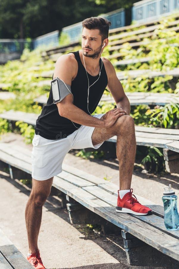 młody sportowiec w słuchawkach z smartphone w działającej armband skrzynce robi ćwiczeniu na ławce obraz stock