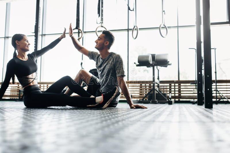 Młody sportowy mężczyzna i schudnięcie dziewczyna siedzimy na podłodze i dajemy pięć w gym zdjęcia royalty free