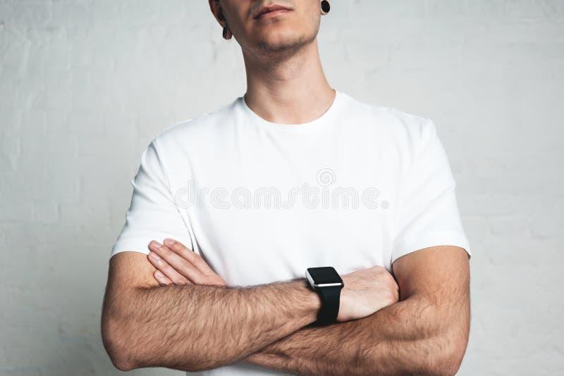 Młody sportowy mężczyzna jest ubranym pustą białą koszulkę i mądrze zegarek, fotografia royalty free