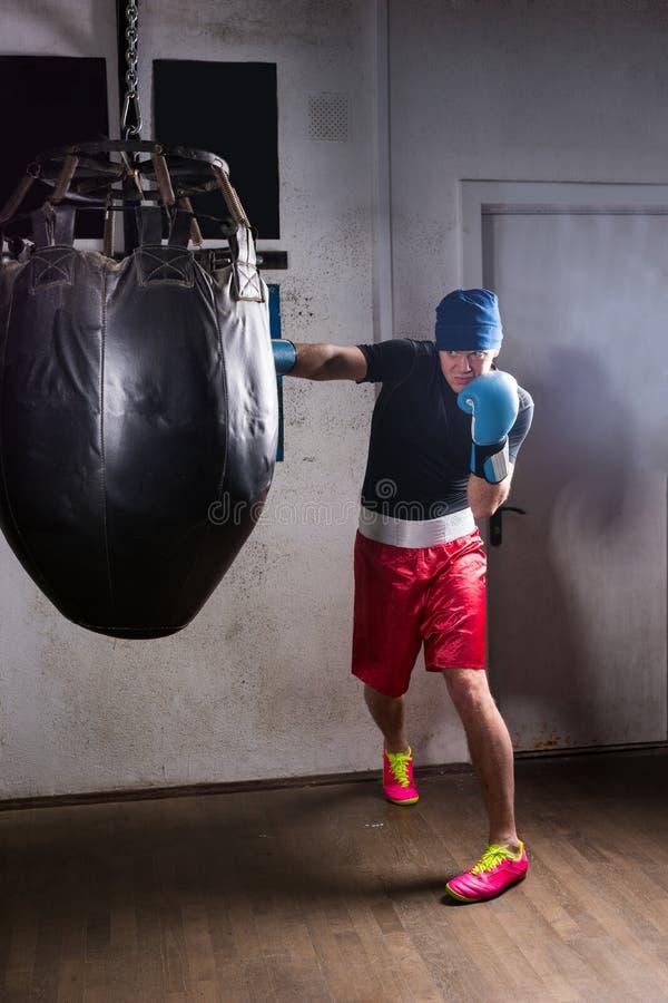 Młody sporty bokser z srogo spojrzeniem w bokserskich rękawiczkach i kapeluszu fotografia stock