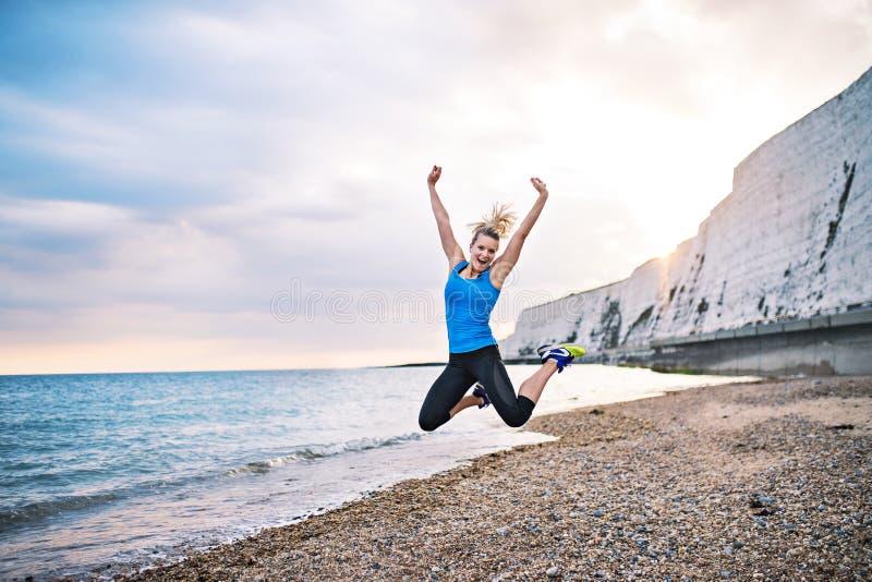Młody sporty kobieta biegacz w błękitnym sportswear doskakiwaniu na plażowym outside zdjęcie stock