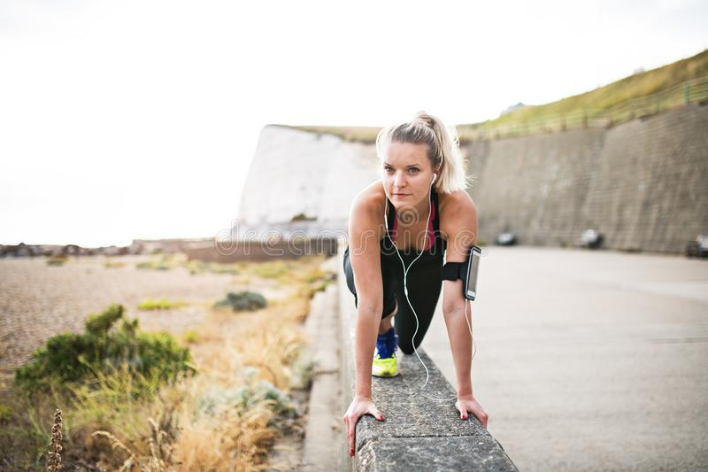 Młody sporty kobieta biegacz z słuchawkami rozciąga outside w naturze zdjęcia stock