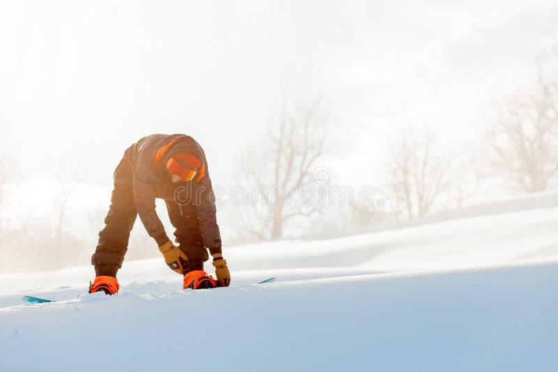 Młody sporty mężczyzna przymocowywa snowboard przed konkursem zdjęcia royalty free