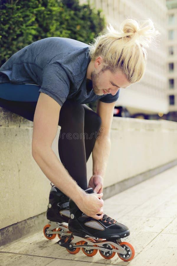 Młody sporty mężczyzna z łyżwiarkami obrazy royalty free