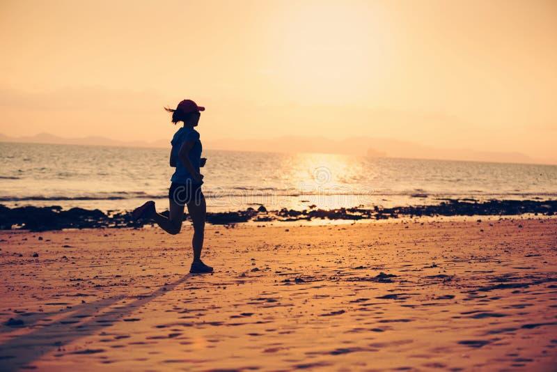 młody sprawności fizycznej kobiety bieg przy zmierzch plażą fotografia stock