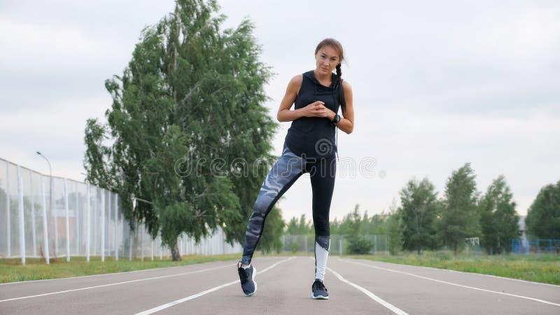 Młody sprawności fizycznej kobiety biegacza rozciąganie iść na piechotę na stadium śladzie obraz royalty free