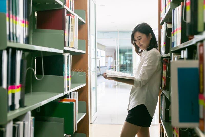 Młody studencki czytanie książka w bibliotece obraz royalty free