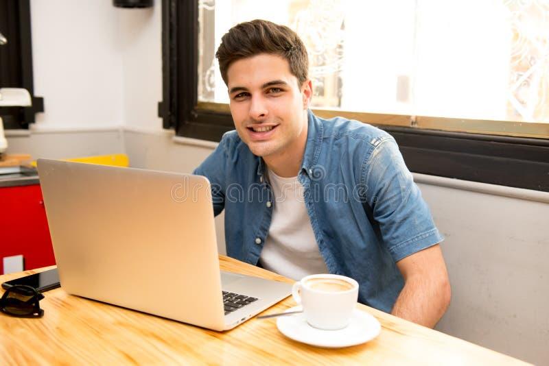 Młody studencki mężczyzna działanie, studiowanie na komputerze w sklep z kawą i zdjęcia stock