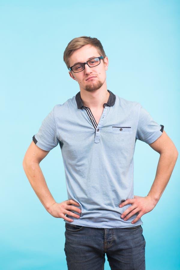 Młody studencki mężczyzna na błękitnym tle Elegancki facet jest ubranym szkła i patrzeje kamerę obrazy royalty free