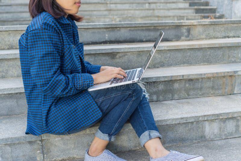 Młody studencki obsiadanie na schodków krokach w kampusie, pisać na maszynie na laptopie fotografia stock