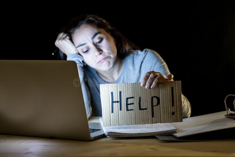 Młody studencki pracujący przy nocą na jej komputerowym mieniu póżno pomoc znak zdjęcie royalty free