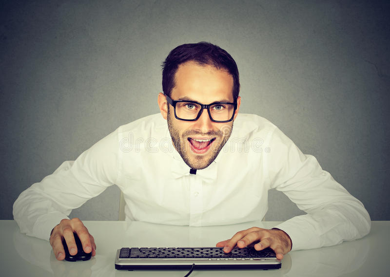 Młody szalony przyglądający biznesmen pisać na maszynie na klawiaturze z szkłami obrazy royalty free