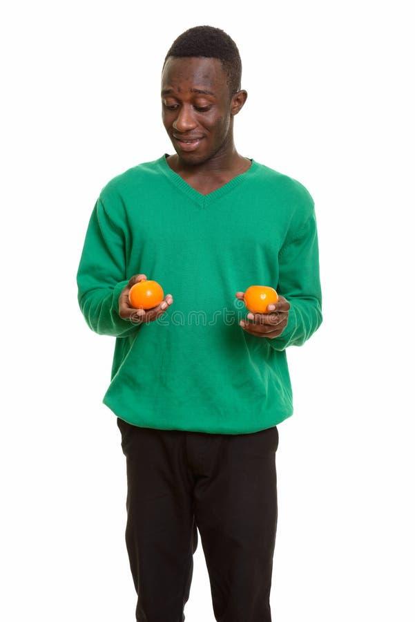 Młody szczęśliwy Afrykański mężczyzna uśmiecha się dwa pomarańcze i trzyma zdjęcie royalty free