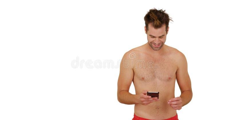 Młody szczęśliwy biały facet z smartphone przed białym tłem w swimsuit zdjęcie royalty free
