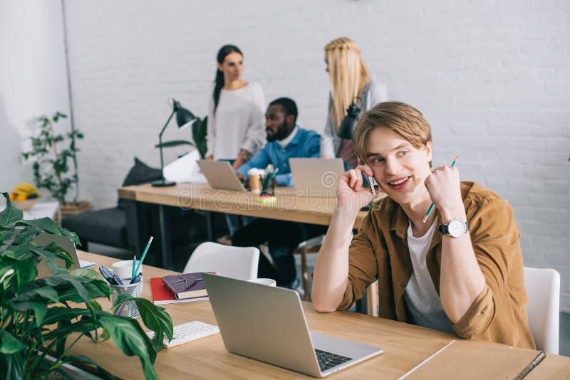 młody szczęśliwy biznesmen gestykuluje i opowiada na smartphone i coworkers pracuje za nowożytnym w obraz stock