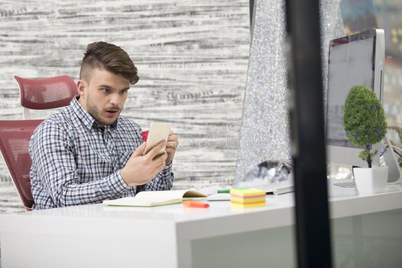 Młody szczęśliwy biznesmen ono uśmiecha się podczas gdy czytający jego smartphone zdjęcia stock
