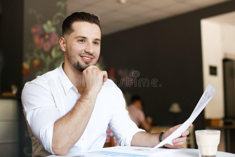 Młody szczęśliwy biznesmen pracuje z dokumentami przy kawiarnią obrazy royalty free