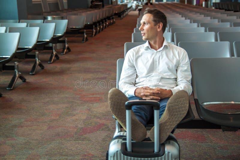 Młody szczęśliwy biznesowy mężczyzna czekać na jego lot w białej koszula obraz stock
