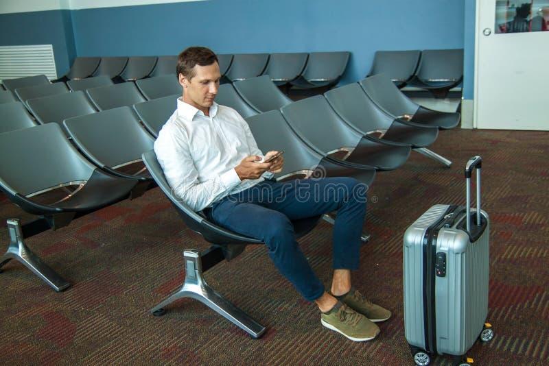 Młody szczęśliwy biznesowy mężczyzna czekać na jego lot w białej koszula fotografia royalty free