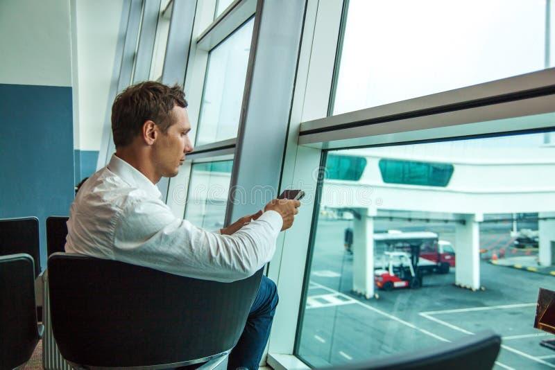 Młody szczęśliwy biznesowy mężczyzna czekać na jego lot w białej koszula obrazy royalty free