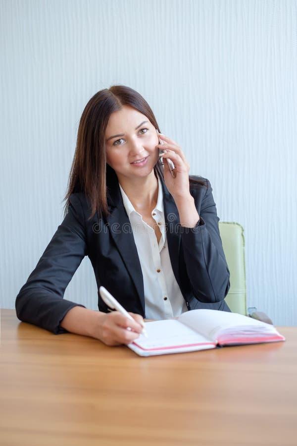 Młody szczęśliwy bizneswoman opowiada na telefonie i pisze notatkach w biurze zdjęcia stock