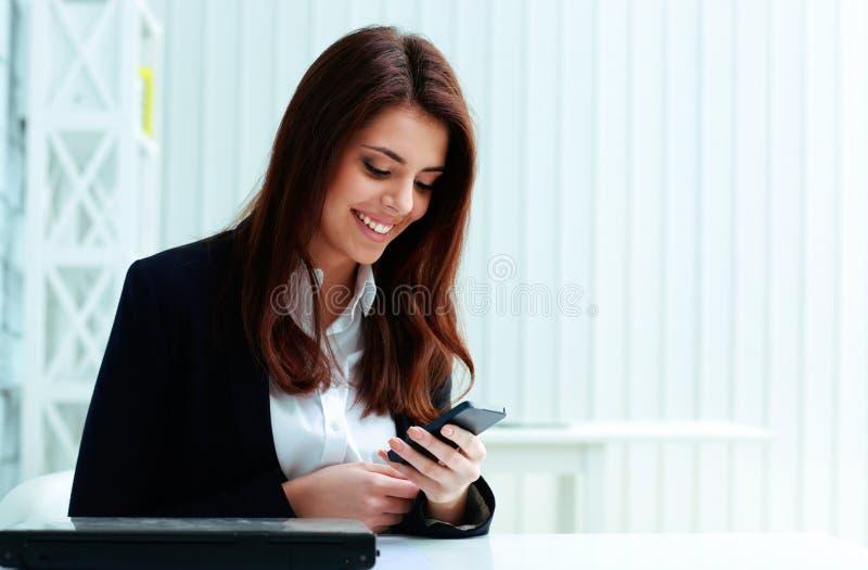 Młody szczęśliwy bizneswoman pisać na maszynie na jej smartphone obrazy stock