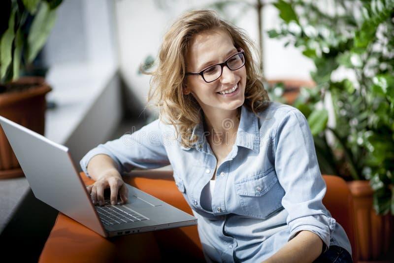 Młody szczęśliwy bizneswoman używa laptop w biurze fotografia stock