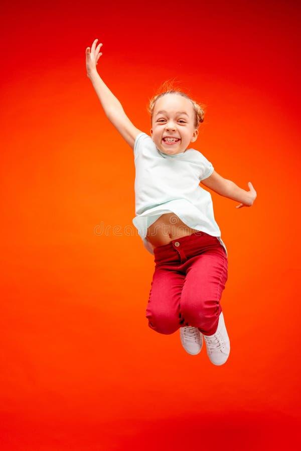 Młody szczęśliwy caucasian nastoletni dziewczyny doskakiwanie w powietrzu na czerwonym pracownianym tle, fotografia stock