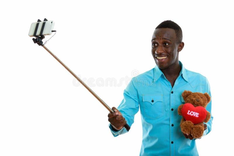 Młody szczęśliwy czarnego afrykanina mężczyzna uśmiecha się misia dowcip i trzyma zdjęcia royalty free