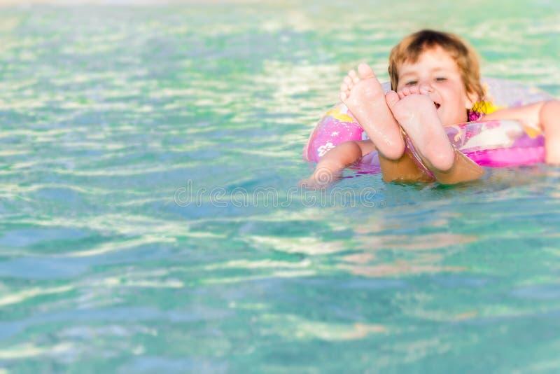 Młody szczęśliwy dziecka dopłynięcie w morzu w spławowym pierścionku na tropie zdjęcie royalty free