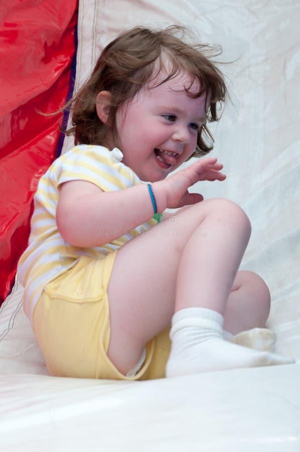 Młody szczęśliwy dziewczyny dziecko jedzie nadmuchiwanego obruszenie outdoors na ciepłym letnim dniu obraz stock