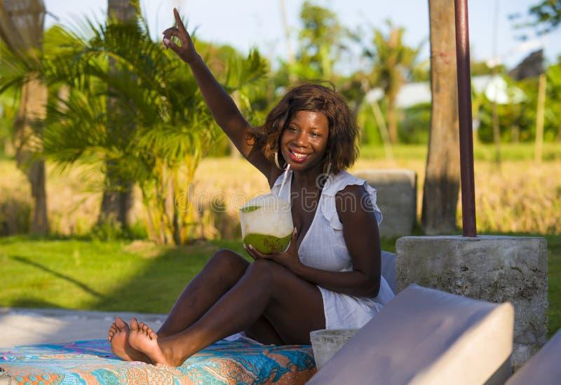 Młody szczęśliwy i atrakcyjny czarny afro Amerykański kobiety lying on the beach na basenu hamaku przy tropikalną miejscowością n fotografia stock