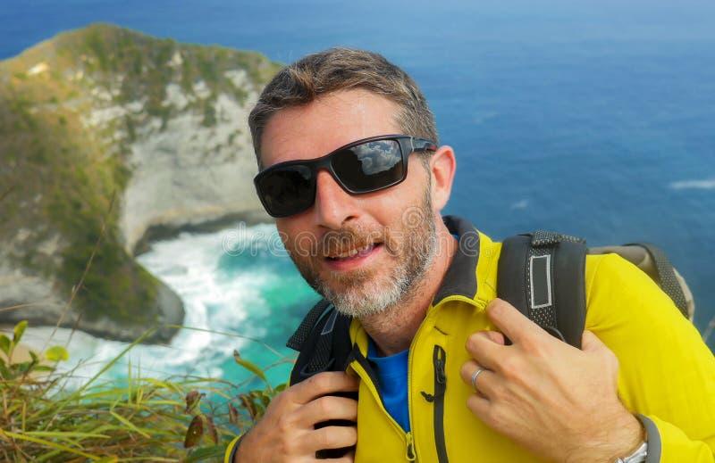 Młody szczęśliwy i atrakcyjny sporty wycieczkowicza mężczyzna wycieczkuje przy dennym faleza krajobrazu uczuciem swobodnie cieszy obrazy stock