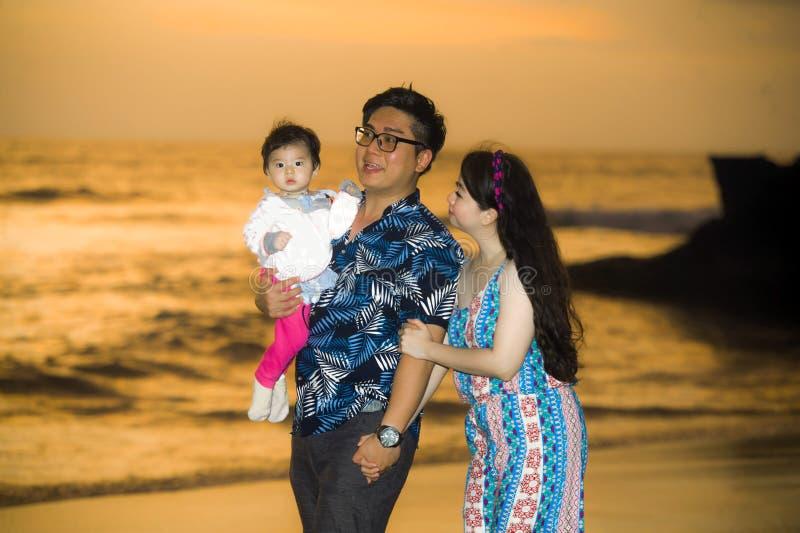 Młody szczęśliwy i piękny Azjatycki Chiński pary mienia dziewczynki córki odprowadzenie na zmierzchu plażowym cieszący się wpólni obrazy stock