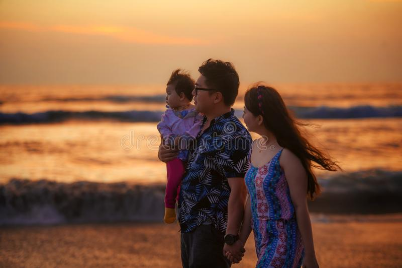 Młody szczęśliwy i piękny Azjatycki Chiński pary mienia dziewczynki córki odprowadzenie na zmierzchu plażowym cieszący się wpólni zdjęcie royalty free