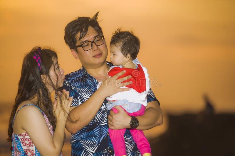 Młody szczęśliwy i piękny Azjatycki Chiński pary mienia dziewczynki córki odprowadzenie na zmierzchu plażowym cieszący się wpólni zdjęcia royalty free
