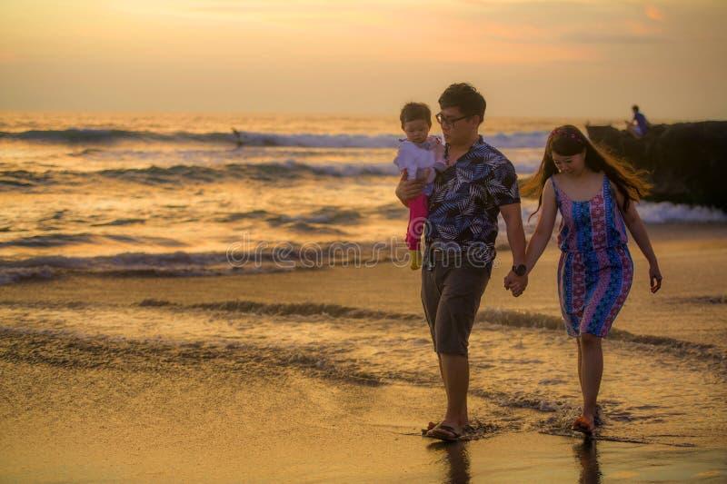 Młody szczęśliwy i piękny Azjatycki Chiński pary mienia dziewczynki córki odprowadzenie na zmierzchu plażowym cieszący się wpólni zdjęcie stock