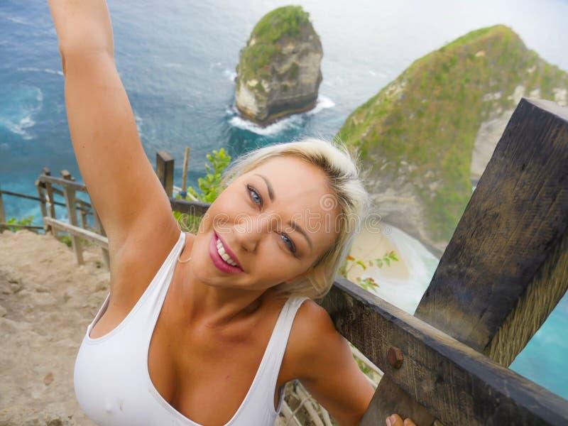 Młody szczęśliwy i piękny blond kobiety ono uśmiecha się rozochocony przy tropikalnej plażowej falezy wakacji letnich krajobrazow fotografia royalty free