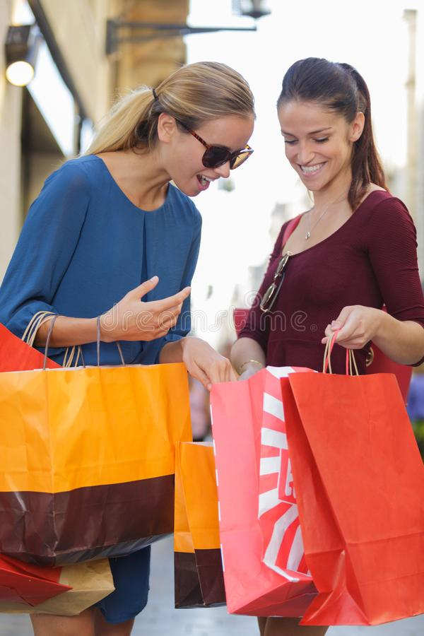 Młody szczęśliwy i zamożny kobiet robić zakupy zdjęcie royalty free
