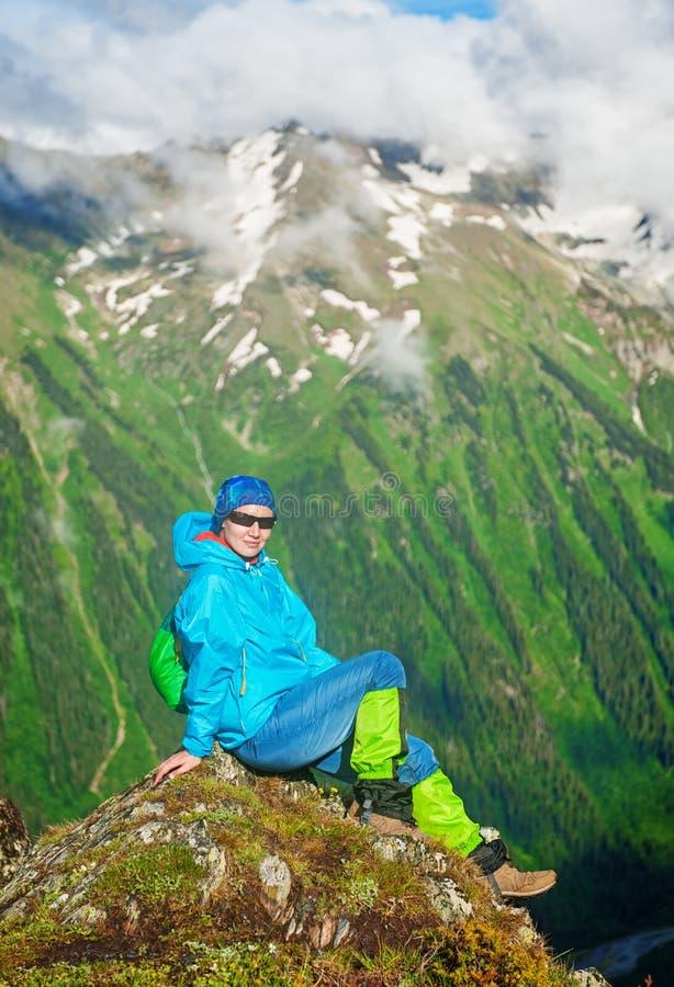 Młody szczęśliwy kobieta wycieczkowicza obsiadanie na wierzchołku góra obrazy stock