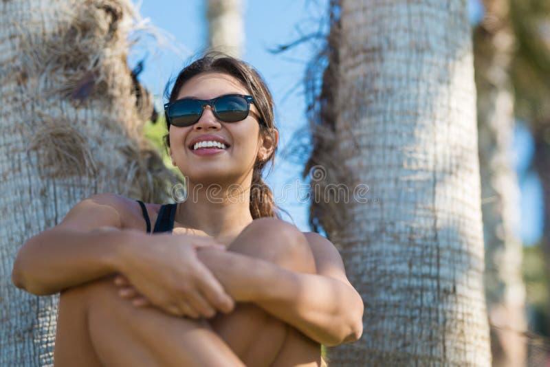 Młody szczęśliwy kobiety obsiadanie z krzyżuję nóg śmiać się obraz royalty free